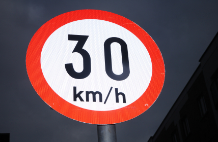 An Irish 30 kmh speed sign in the dark night sky.